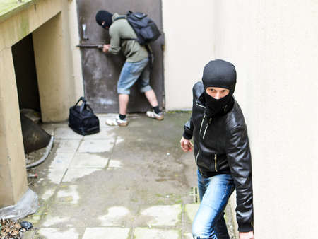Burglary  One burglar tries open the door  Second is on the lookout photo