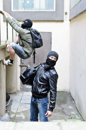 Escape from a robbery  One tries to climb on the rails  Second is on the lookout Stock Photo - 13559106