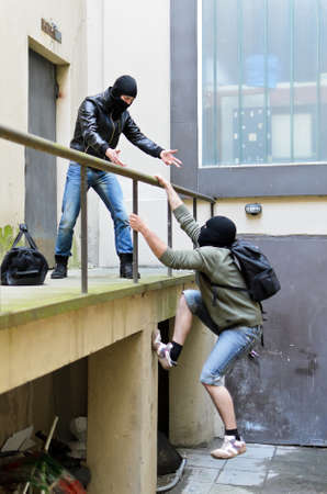Escape from a robbery  One tries to help another to climb the rails  Stock Photo - 13559115