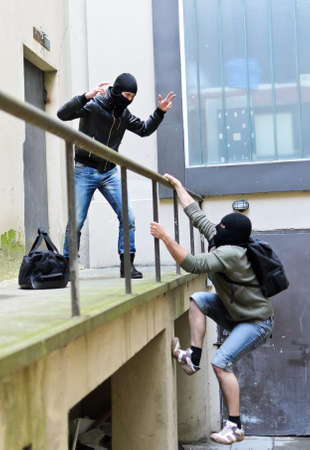 Escape from a robbery  One tries to help another to climb the rails  Stock Photo - 13559111