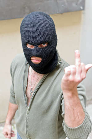 show off: Burglar wearing a mask shows fuck gesture. Stock Photo