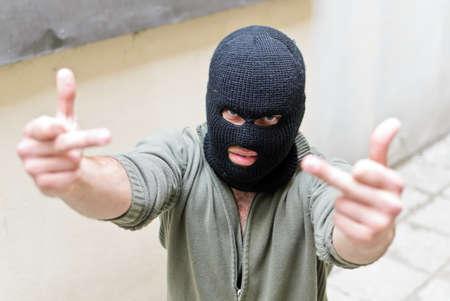 Burglar wearing a mask shows fuck gesture. photo