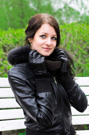 Attractive girl sitting on a park bench photo