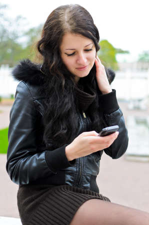 Attractive girl writing an sms in park. photo