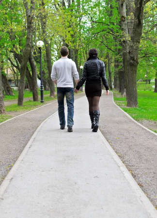 Couple walking down the road in the park  From the back photo