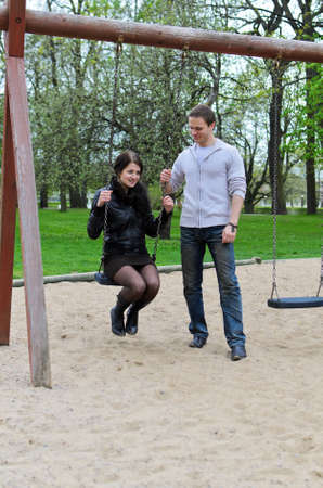 Guy rolls a girl on a swing in the park  photo
