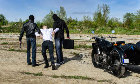 balaclava: Two bandits kidnapped a businessman with a suitcase Stock Photo