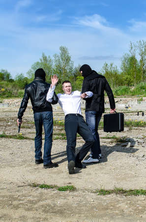 Two bandits kidnapped a businessman with a suitcase Stock Photo - 13758896