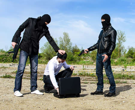 Two bandits kidnapped a businessman with a suitcase Stock Photo - 13758886