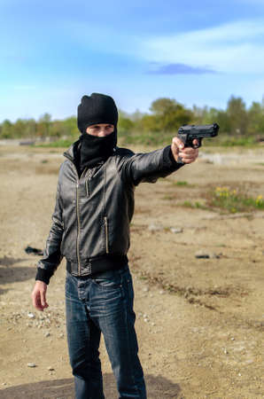 Masked gunman taking aim with a gun Stock Photo - 13758848