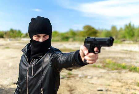 male killer: Masked gunman taking aim with a gun