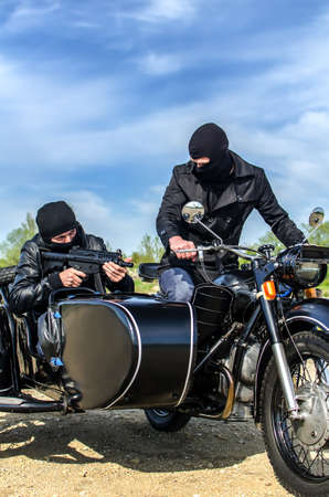 Two armed men riding a motorcycle with a sidecar photo