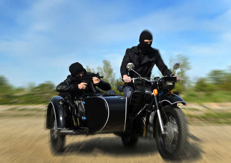 Two armed men riding a motorcycle with a sidecar. Motion blur. Stock Photo