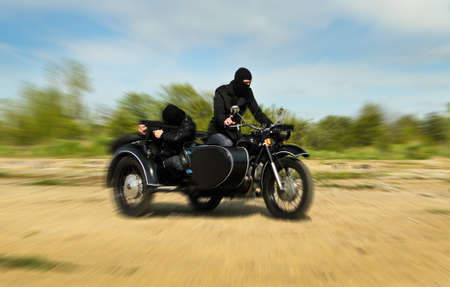 sidecar: Two armed men riding a motorcycle with a sidecar. Motion blur. Stock Photo