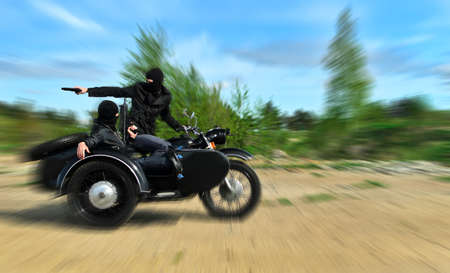 Two armed men riding a motorcycle with a sidecar. Motion blur. photo