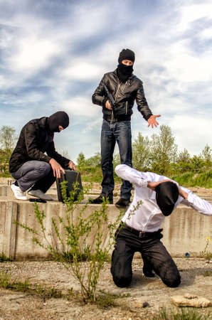 Two masked gunman trying to kill businessman. Asks a PIN Stock Photo - 13758859