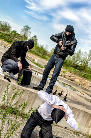 Two masked gunman trying to kill businessman. Asks a PIN Stock Photo - 13758910