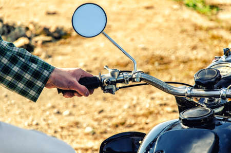 Man's hand rests on the steering wheel motorcycle photo