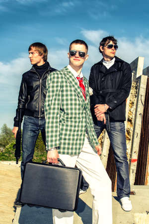 Mafia: Three thugs with a suitcase and weapons photo