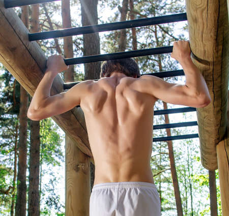 pullups: Man pull-ups on a bar in a forest. From the back. Stock Photo