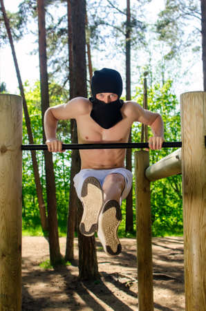 Antiglobalist trains, pull-ups on a bar in a forest photo