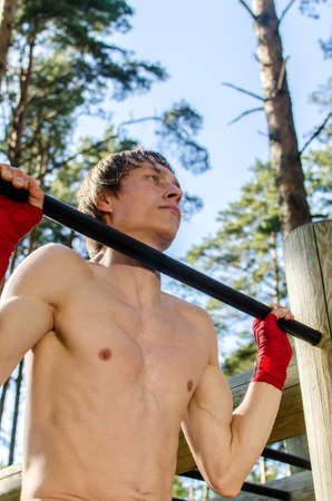 pullups: Attractive man pull-ups on a bar in a forest Stock Photo
