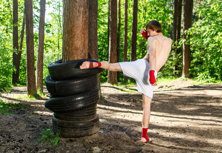 training wheels: Fighter kicking rubber wheels with the leg Stock Photo