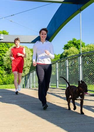 mujer perro: Pareja corriendo con el perro por el puente