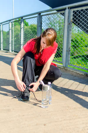 Female runner stopped to tie his shoelaces photo