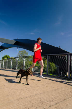 Sportsman and dog running outdoors photo