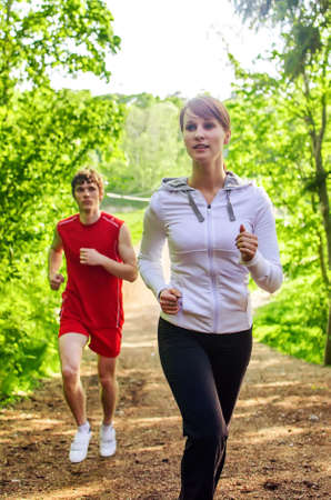 Man and woman running along the forest path photo
