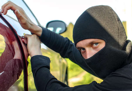 Thief in the mask breaks the door in the car photo
