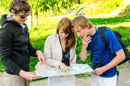 3 persons: Three friends traveling, they look at a map Stock Photo