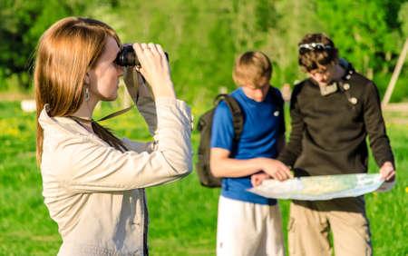 Three friends traveling  Girl looking through binoculars photo
