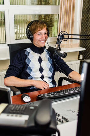 Anchorman sitting in front of a microphone on the radio photo