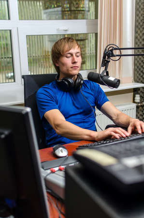 Dj working in front of a microphone on the radio photo