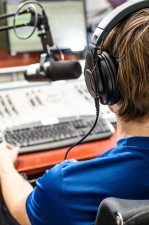 radio microphone: Dj working in front of a microphone on the radio, from the back