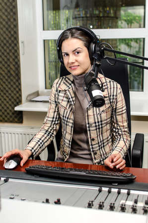 newsreader: Anchorwoman sitting in front of a microphone on the radio