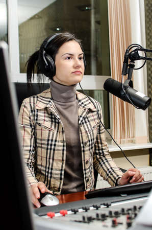 hosts: Anchorwoman sitting in front of a microphone on the radio