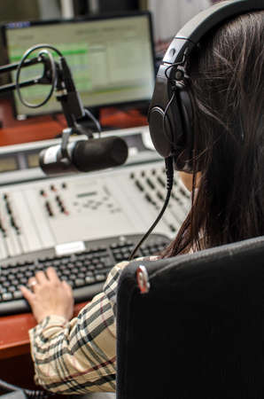 Anchorwoman sitting in front of a microphone on the radio, from the back photo