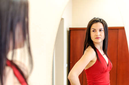 Beautiful girl in red dress posing in front of a mirror Stock Photo - 13982124
