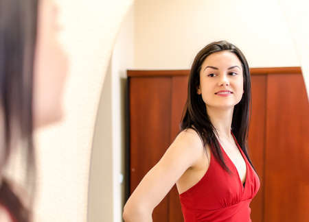 Beautiful smiling girl in red dress posing in front of a mirror Stock Photo - 13982115