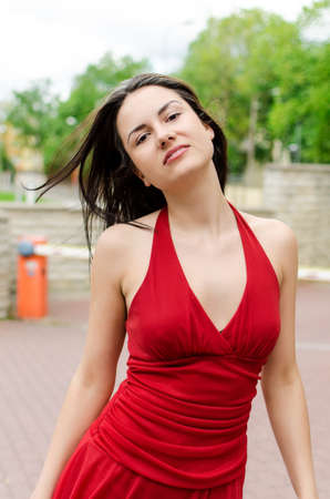 Beautiful girl in red dress posing on the street Stock Photo - 13982222