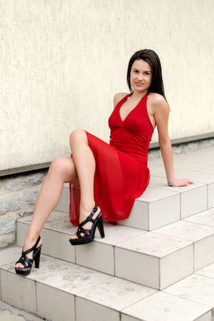Beautiful girl in red dress posing on the stairs photo