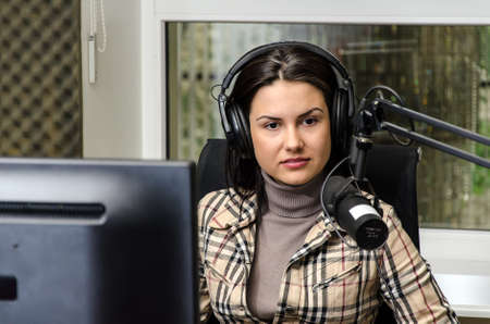 hosts: Anchorwoman in front of a microphone on the radio Stock Photo