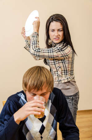 hitting: Domestic violence: Wife trying to beat her husband with a plate Stock Photo