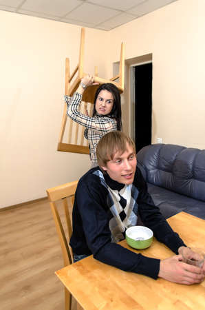 Domestic violence: Wife trying to beat her husband with a chair photo