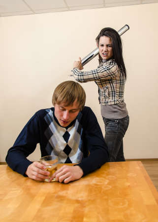 Domestic violence  Wife trying to beat her husband with a metal rod photo