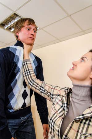 stifle: Office fight  Woman trying to stifle a man Stock Photo