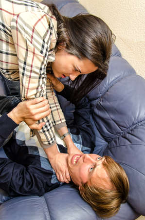 Office fight  Woman trying to stifle a man on the sofa photo